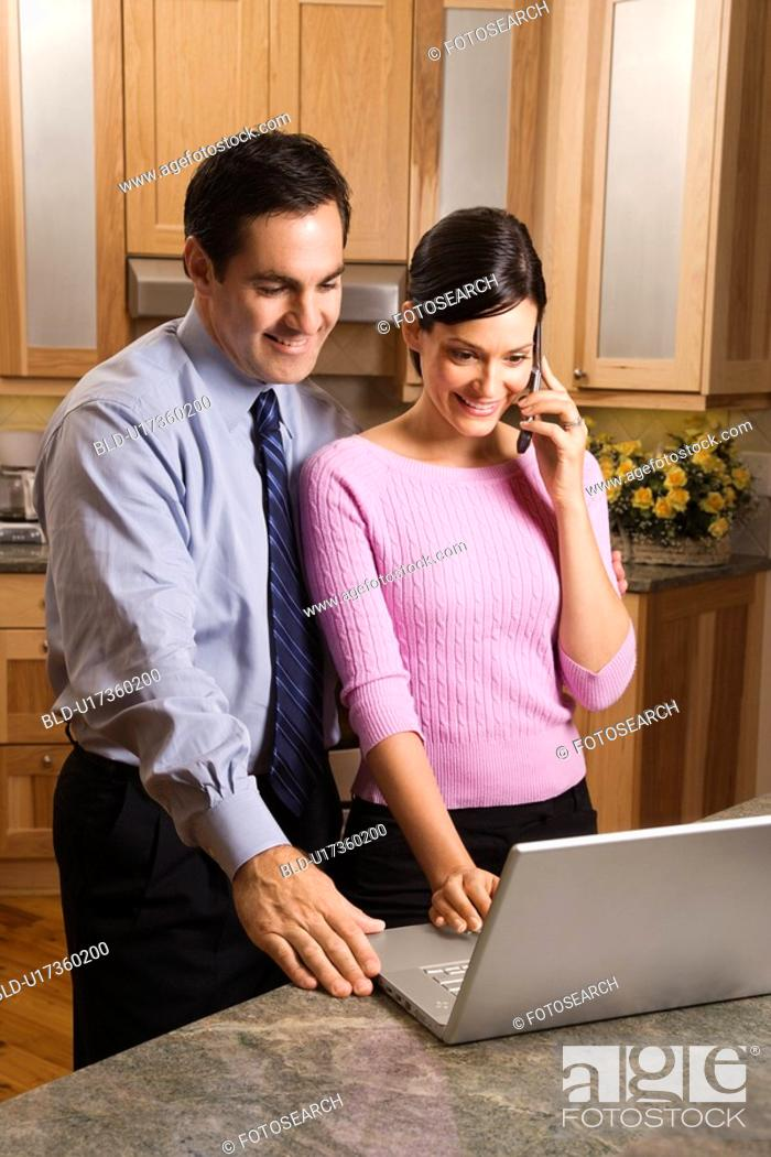 Stock Photo: MId-adult female talking on phone and mid-adult male both looking at laptop computer in kitchen.