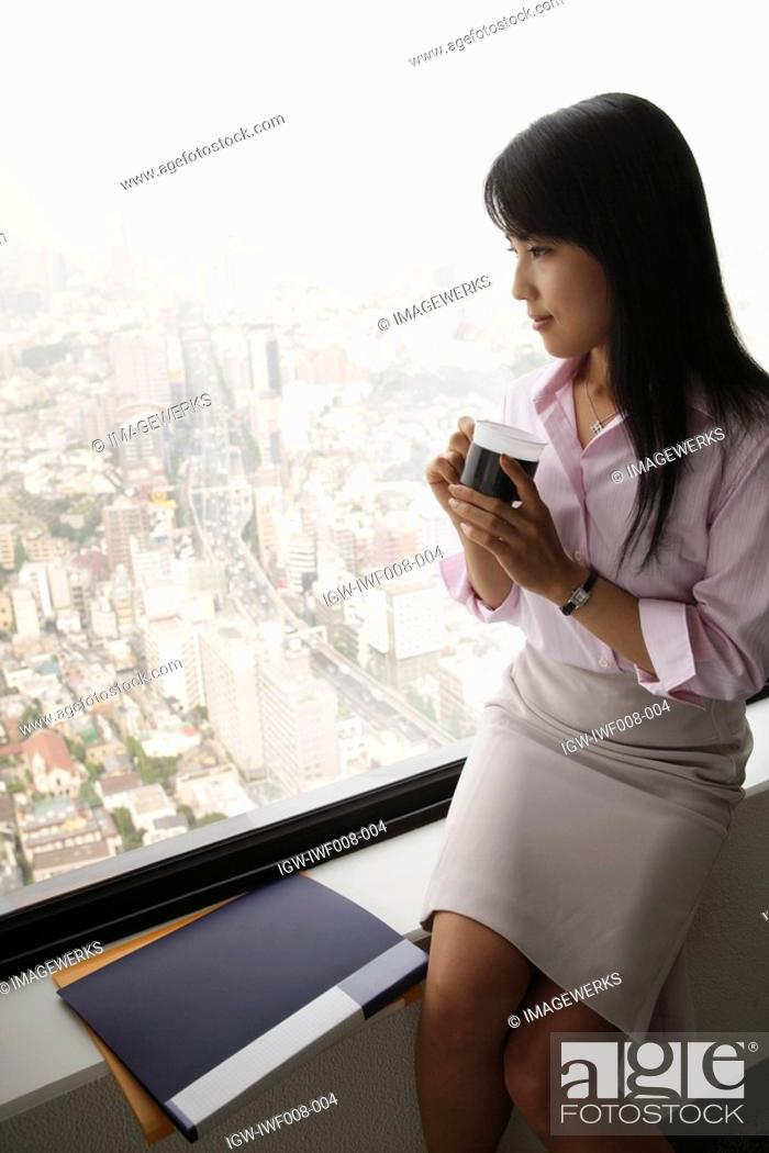 Stock Photo: A woman drinking coffee as she is seated near the window.