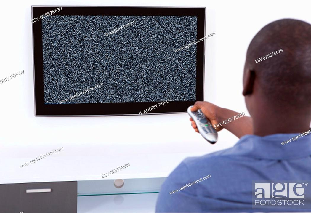 Stock Photo: Rear View Of African Man With Remote In Front Of Television.