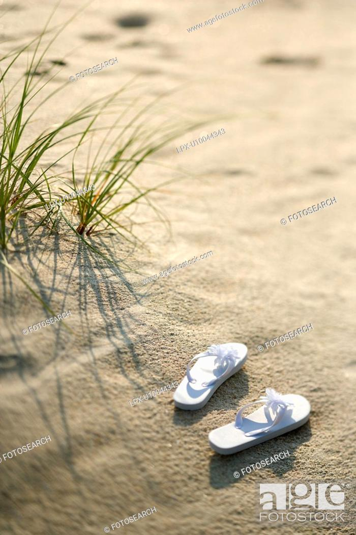 Stock Photo: Two white sandals on sandy beach.