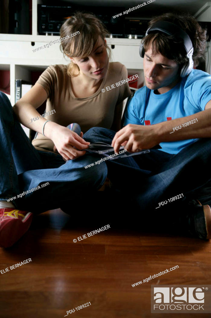 Stock Photo: Young couple looking at CD covers, man wearing headphones.