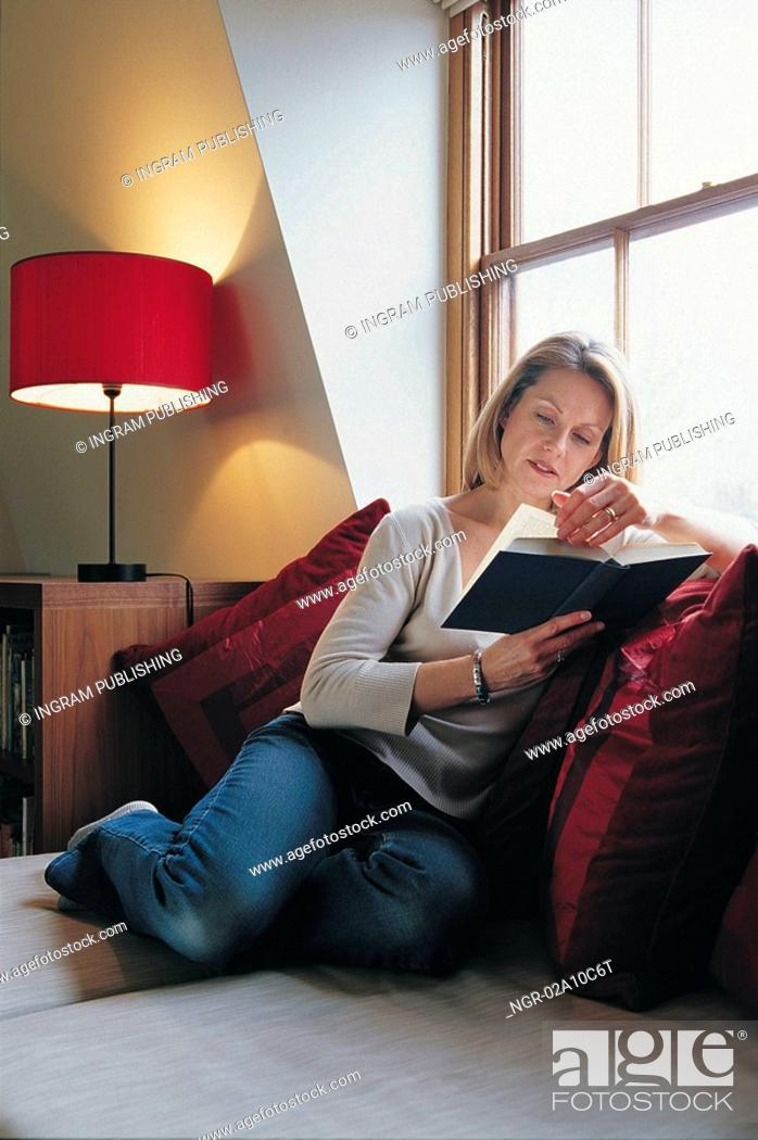 Stock Photo: woman reading by the window.