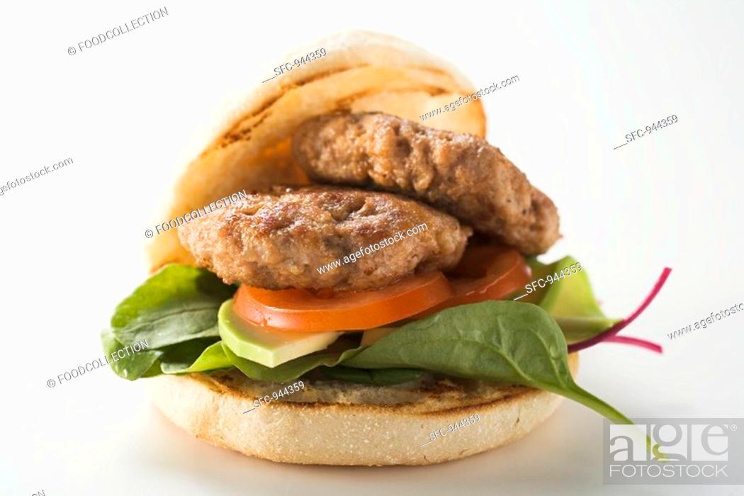 Stock Photo: Meat patties with spinach and avocado in hamburger roll.