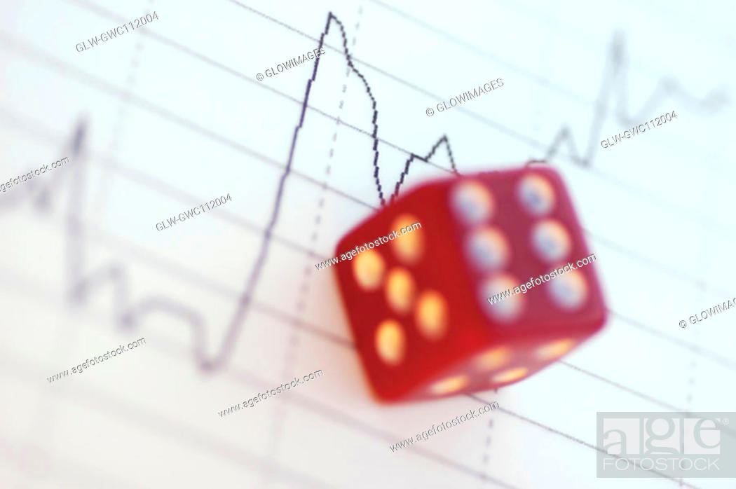 Stock Photo: Close-up of a dice over a line graph.