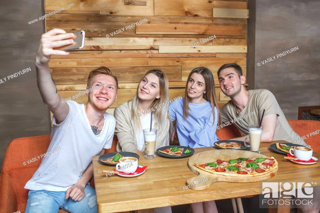 Imagen: Young friends taking selfie while sitting at restaurant.