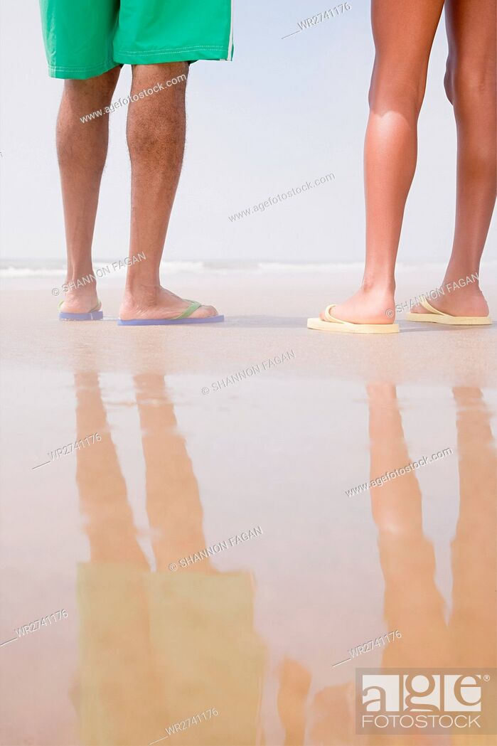 Stock Photo: Two people standing on a beach.