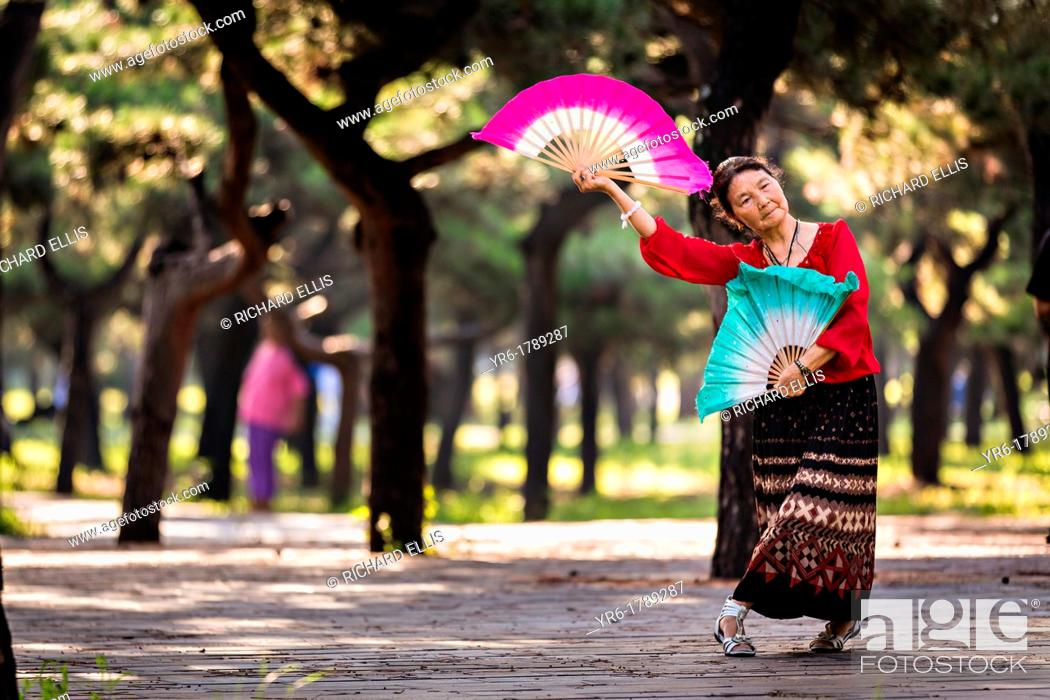 Photo de stock: An elderly Chinese woman practices tai chi fan dance martial arts exercise early morning at the Temple of Heaven Park during summer in Beijing, China.