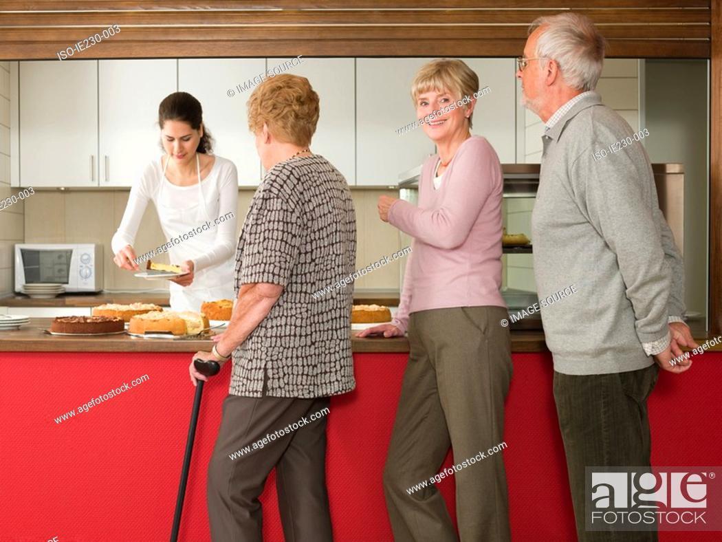 Stock Photo: Seniors queuing for cake.