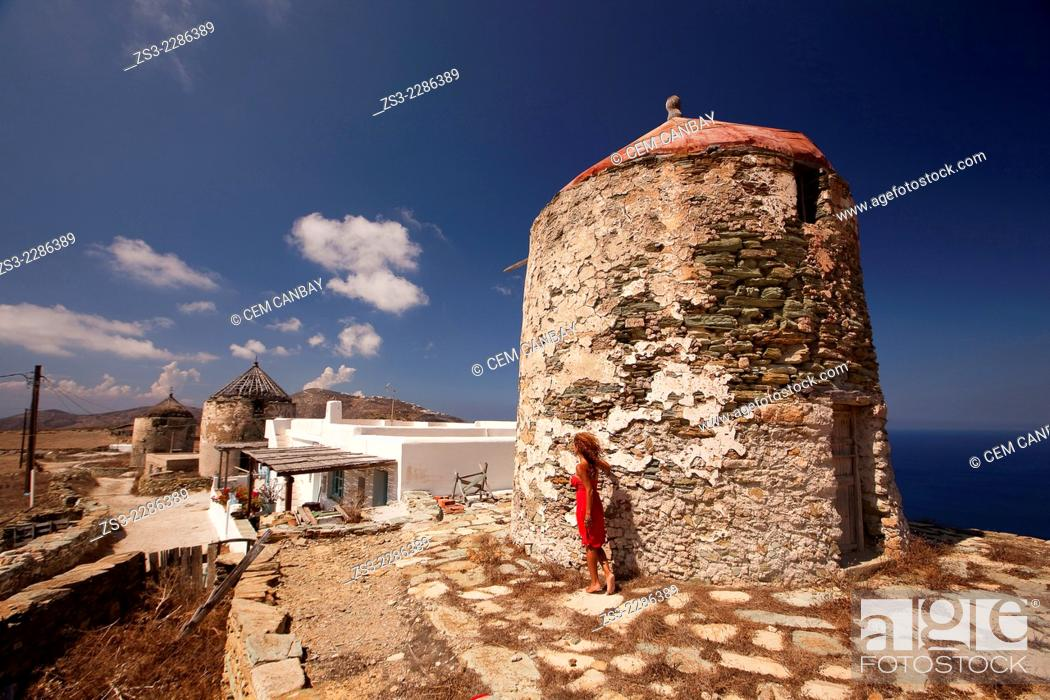 Stock Photo: Woman in front of an old windmill, Folegandros, Cyclades Islands, Greek Islands, Greece, Europe.