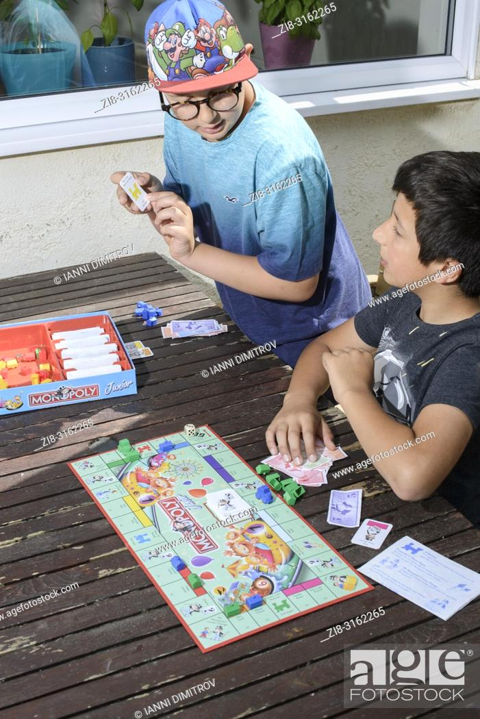 Stock Photo: Boys playing together- monopoly board game, UK.