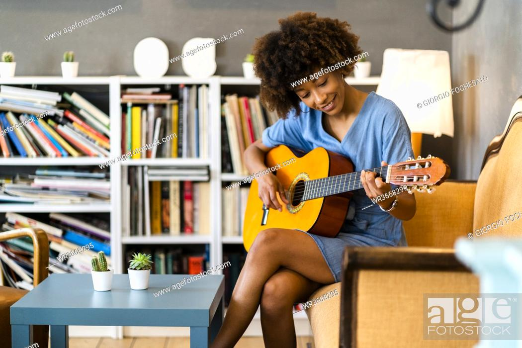 Stock Photo: Happy woman playing guitar while sitting on sofa in coffee shop.