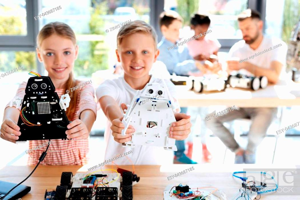 Stock Photo: Talented children. Charming joyful brother and sister standing near the working table during their robotics workshop and showing their robot models.
