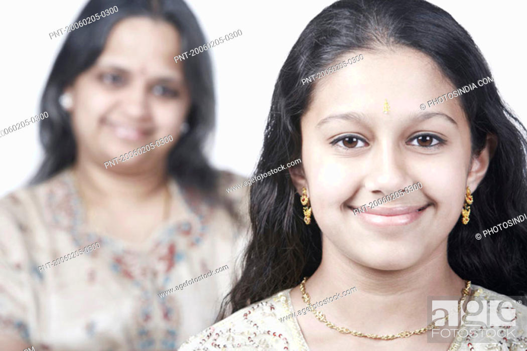 Stock Photo: Portrait of a girl smiling with her mother standing behind her.
