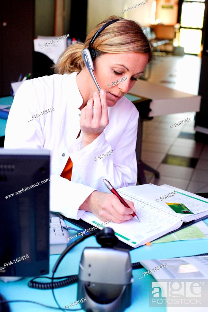 Stock Photo: Medical secretary setting appointments in his diary on the phone.