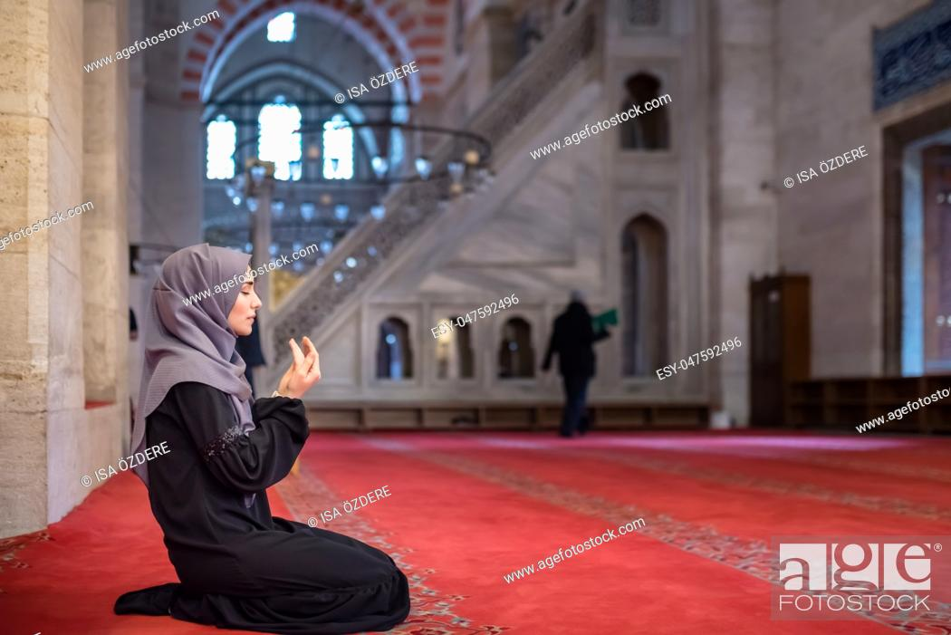 Stock Photo: Muslim woman in headscarf and hijab prays with her hands up in air in mosque. Religion praying concept.
