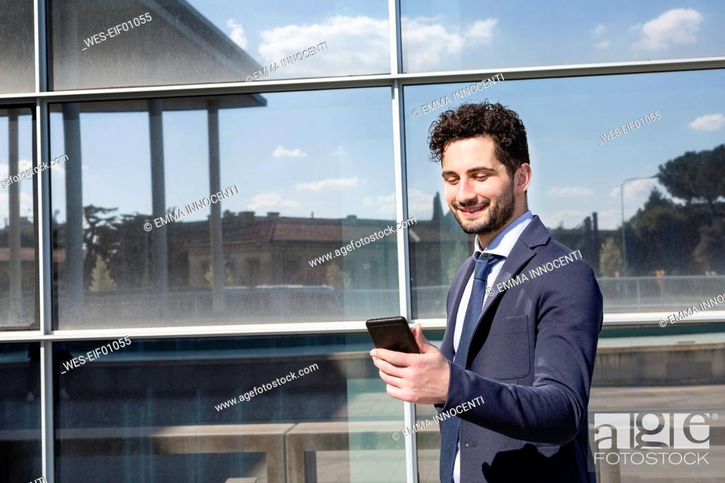 Stock Photo: Male professional using mobile phone while standing in front of building.