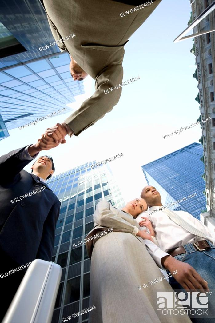 Stock Photo: Low angle view of a businesswoman with her head on a businessman's shoulder and two businessmen shaking hands.