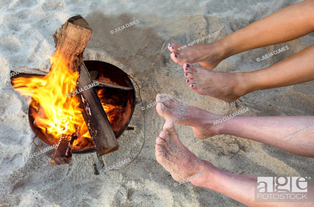 Stock Photo: People Warming Their Feet At A Campfire At The Beach.