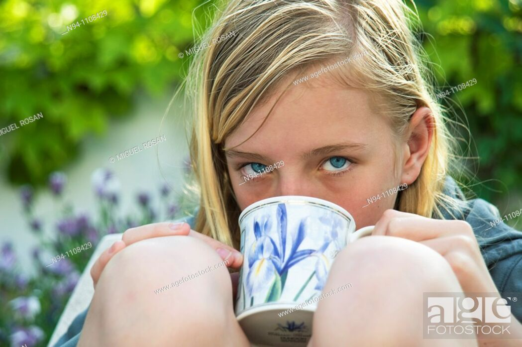 Stock Photo: Close up of teenage girl with a cup of soup in the garden.