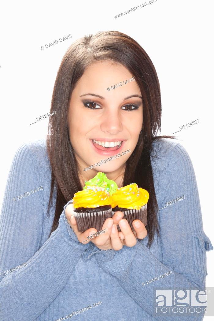 Stock Photo: Beautiful Caucasian woman eating very unhealthy cupcakes.