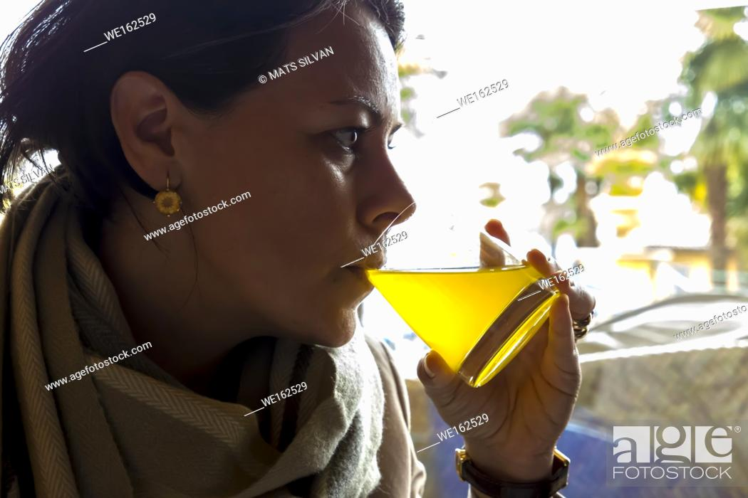 Imagen: Woman Drinking Orange Juice in Switzerland.