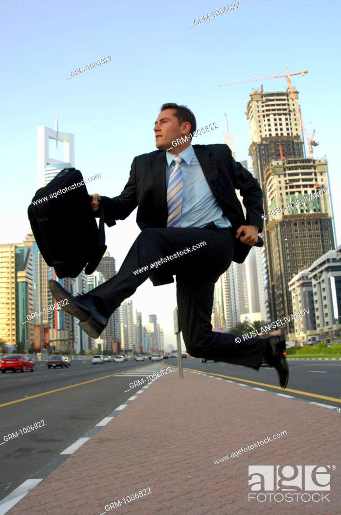 Stock Photo: Businessman jumping in the air on Shaikh Zayed Road in Dubai.