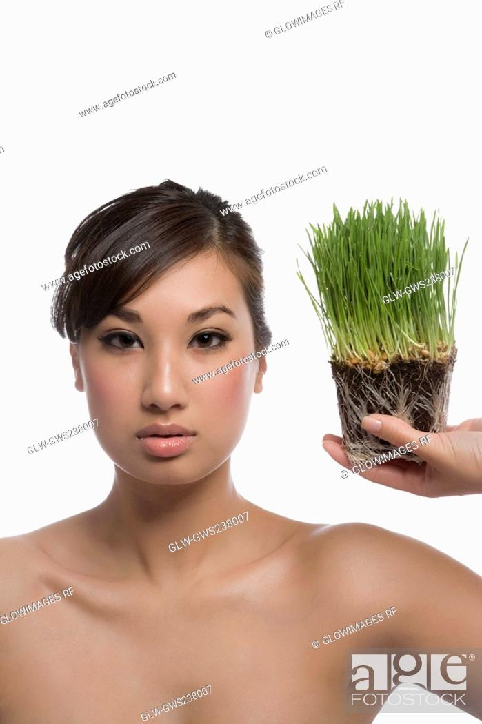 Stock Photo: Portrait of a young woman holding wheatgrass.