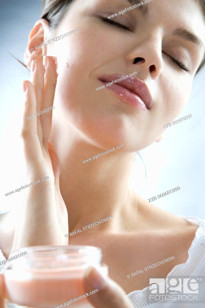 Stock Photo: young woman creaming face.