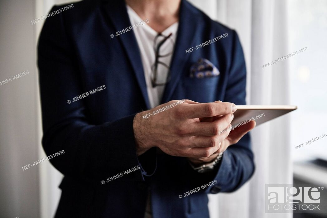 Stock Photo: Man holding digital tablet in office.
