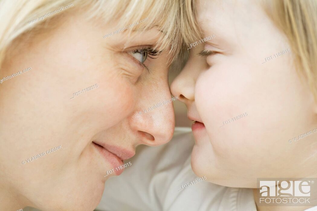 Stock Photo: A mother and daughter lying down, face to face, close-up.
