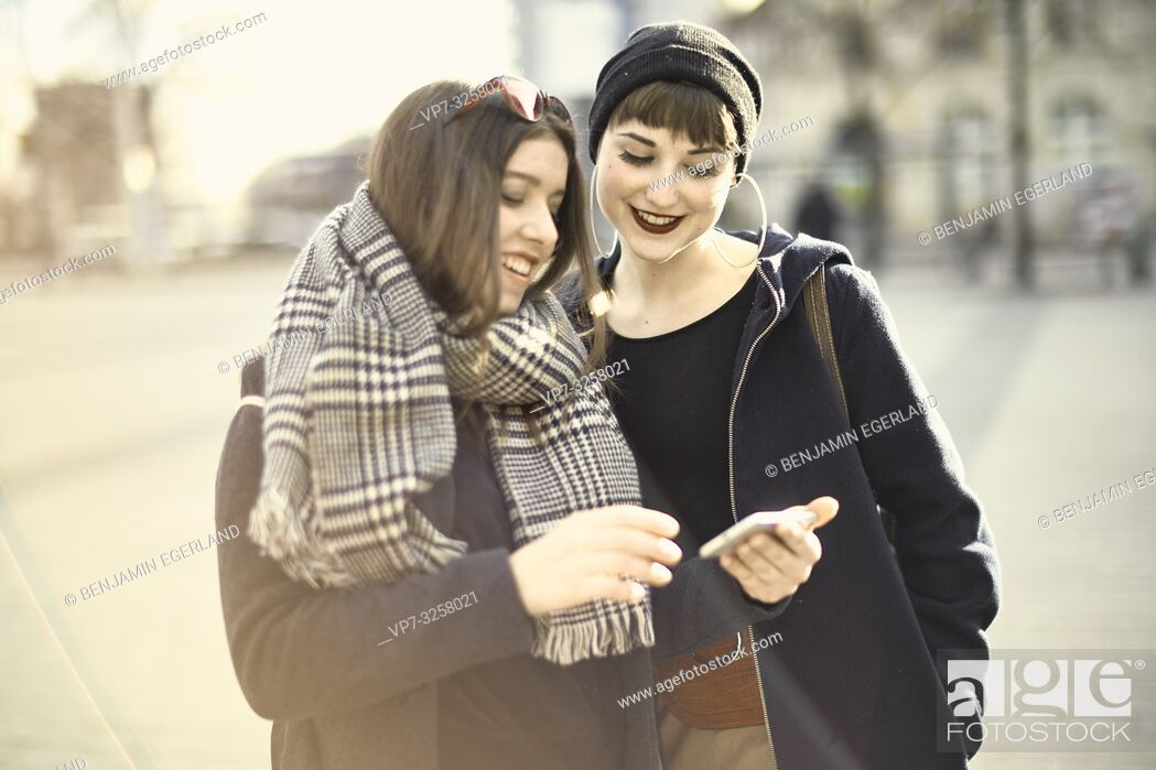 Imagen: two women using smartphone, wearing leisure clothes, in city Cottbus, Brandenburg, Germany.