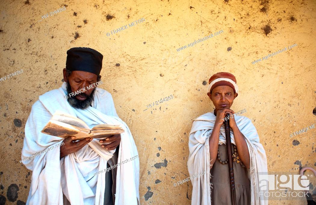 Stock Photo: Orthodox christian man and woman during a mass. The man is reading the bible written in Ge'ez a forerunner of modern Amharic language.