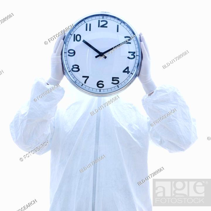 Stock Photo: Man in biohazard suit holding clock in front of face standing against white background.