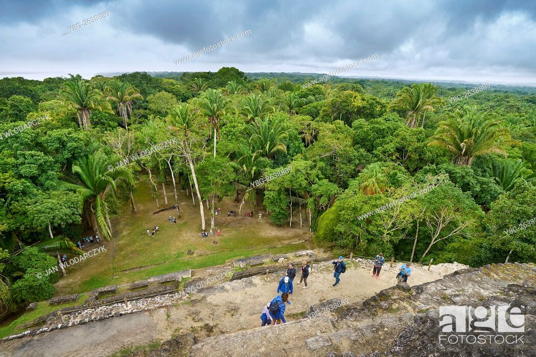 Stock Photo: Tourists admiring the view of Yucatan from the top of High Temple, Ancient Maya Ruins, Lamanai, Belize.