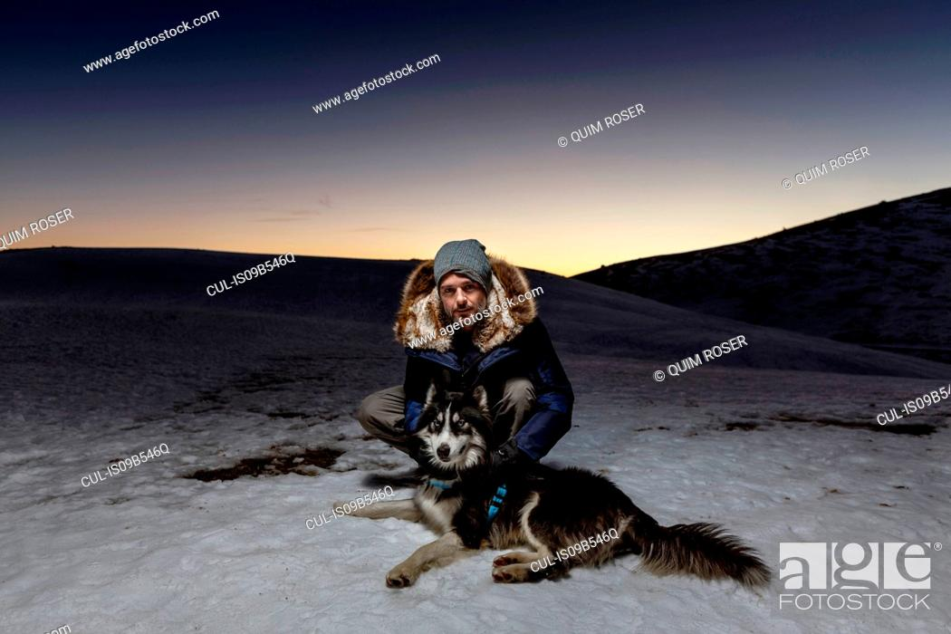 Photo de stock: Portrait of mature man crouching with dog in snow at night.