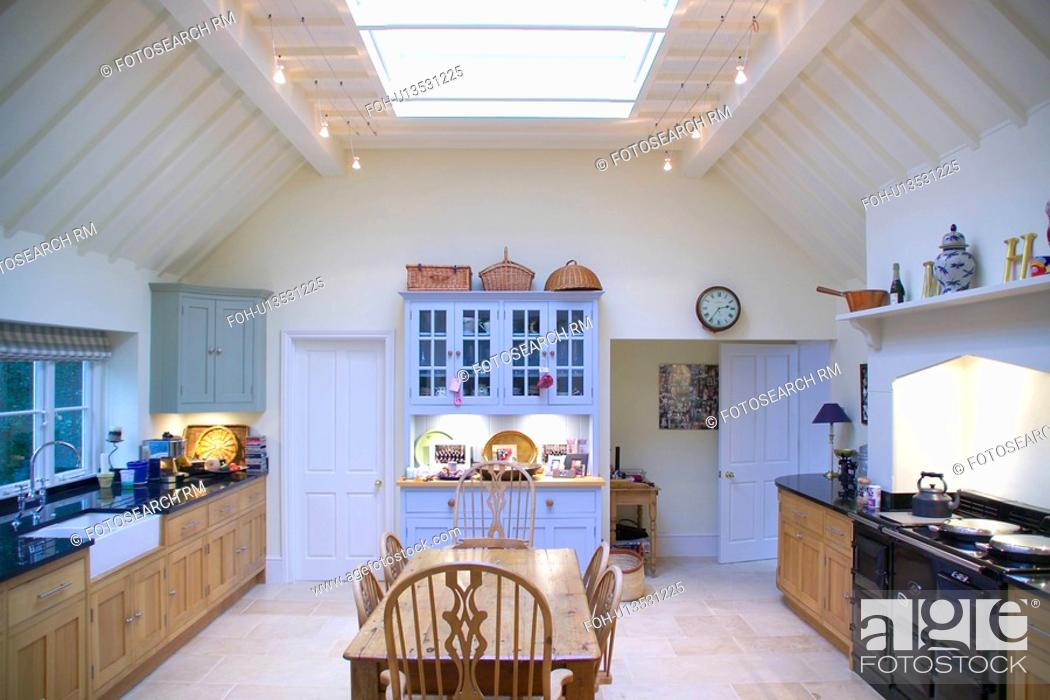 Old Pine Table And Chairs In White Country Kitchen With Black Aga