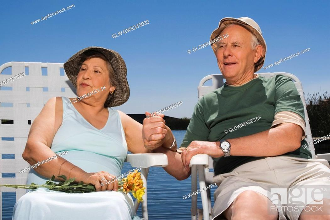 Stock Photo: Senior couple sitting at the lakeside with holding hands of each other.