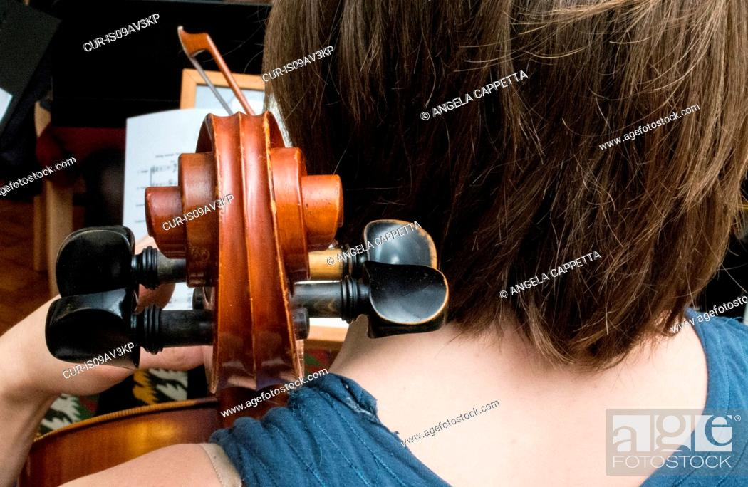 Imagen: Young woman playing cello in string quartet practice, rear view.