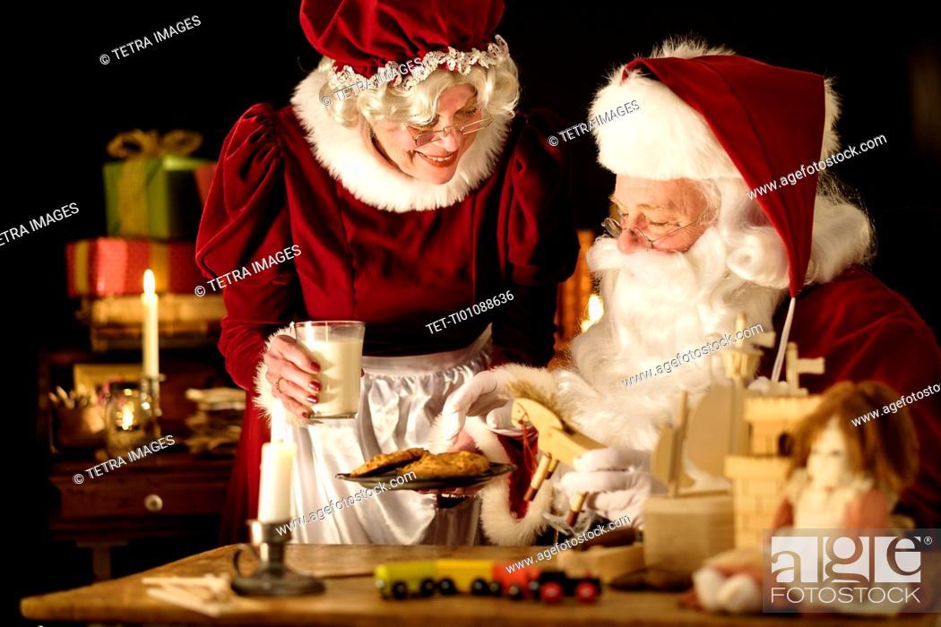Stock Photo Mrs Claus Bringing Homemade Cookies To Santa Claus