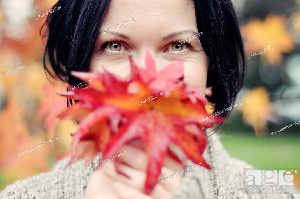 Stock Photo: Smiling mid adult woman holding leaf close to her face.