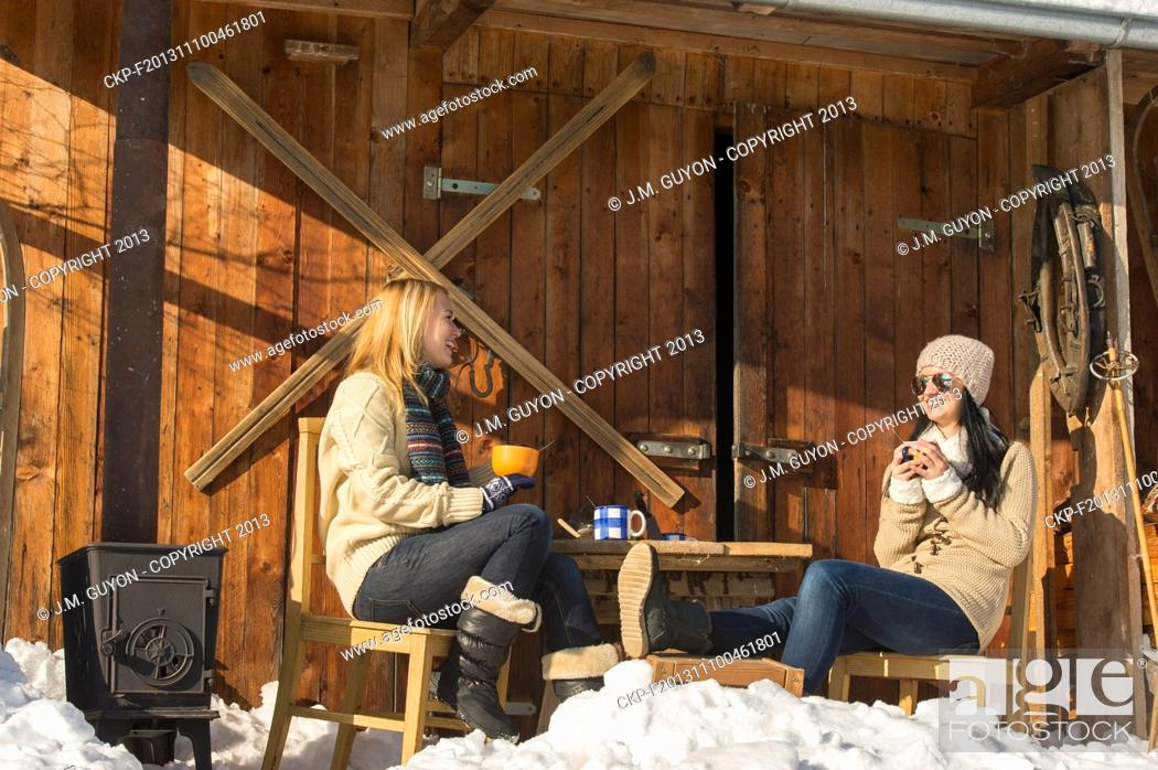 Imagen: Two girlfriends have tea winter snow cottage sunny outdoor.