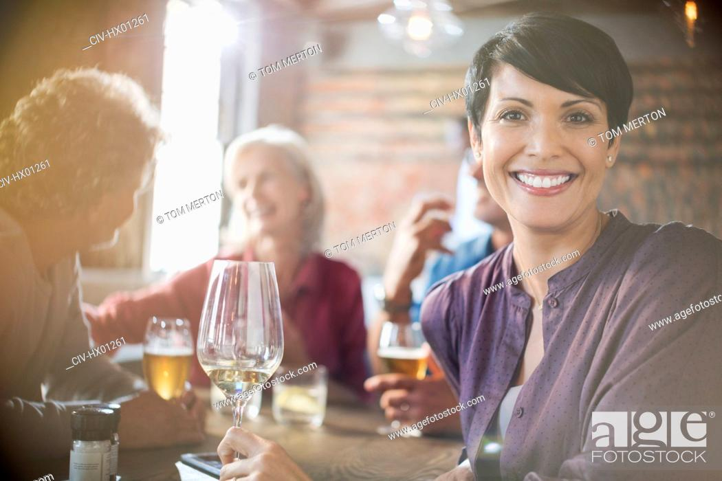Stock Photo: Portrait smiling woman drinking white wine dining with friends at restaurant table.