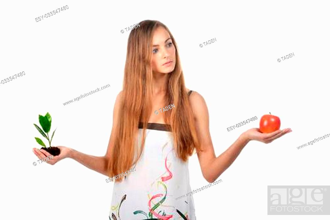 Imagen: Beautiful young woman holding green sprout of tree and apple.