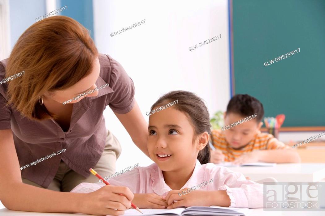 Stock Photo: Close-up of a female teacher teaching a schoolgirl in a classroom.