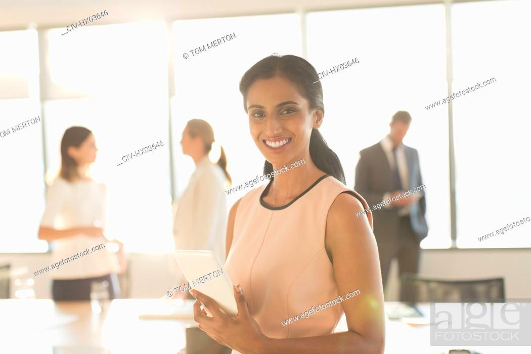 Stock Photo: Portrait smiling, confident businesswoman with digital tablet in conference room.