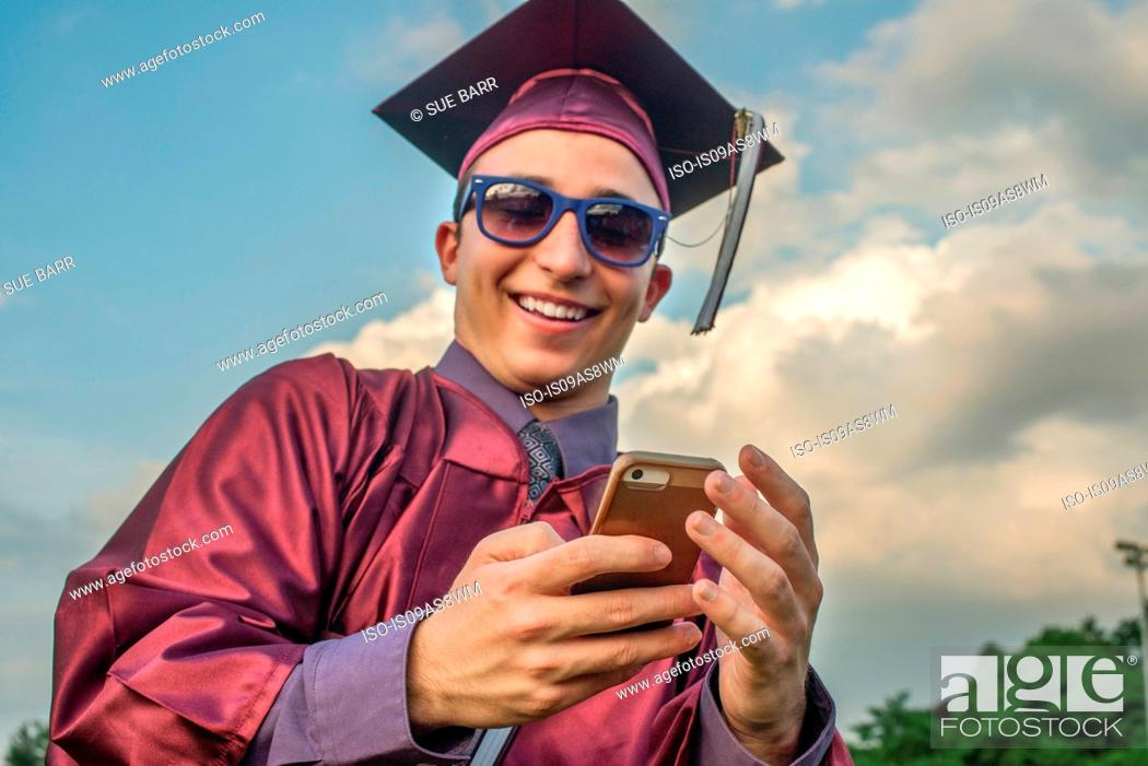 Stock Photo: Graduate taking selfie with smartphone.