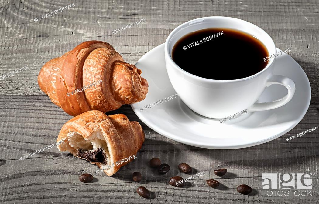 Stock Photo: Coffee and croissants on a wooden table. Broken croissant and coffee beans nearby.