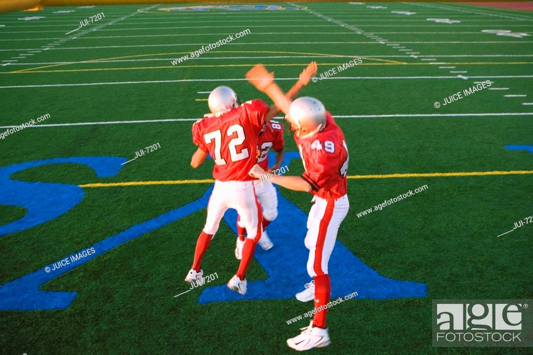 Stock Photo: Three American football players, in red football strips, celebrating touchdown on pitch during competitive game, doing high-fives, elevated view.