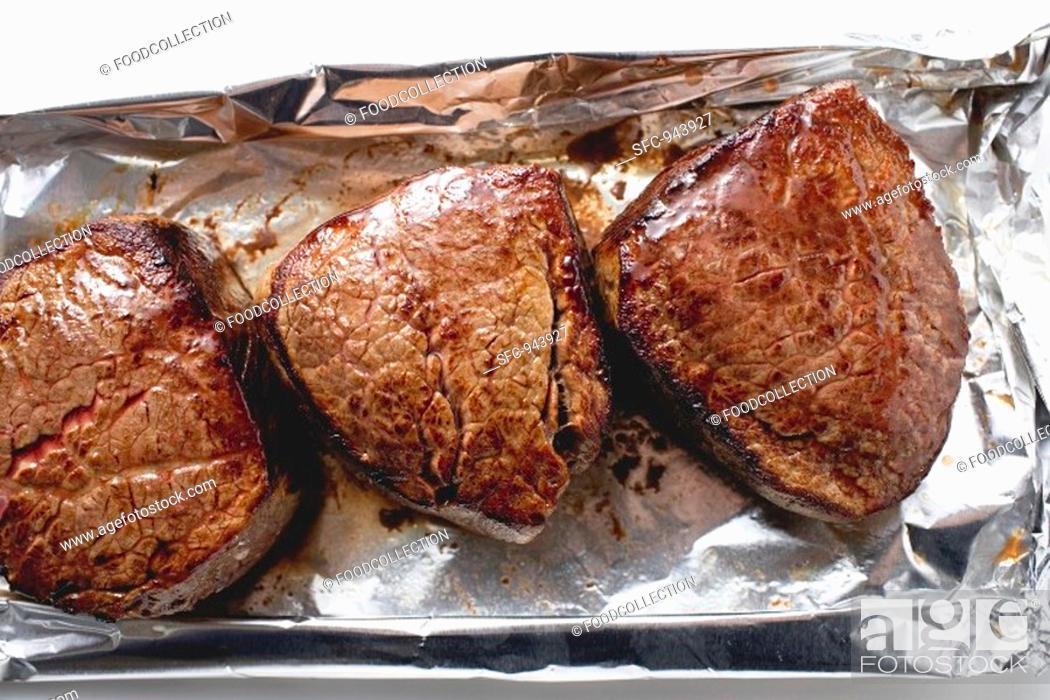 Stock Photo: Three fillet steaks on aluminium foil.