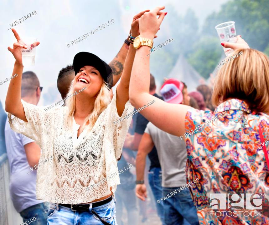 Stock Photo: Beek en Donk, Netherlands, Two girls dancing and laughing at an event.